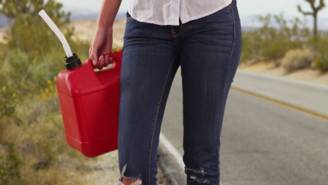 tight shot of waist of woman with gasoline canister standing by desert road - hold me tight stock videos & royalty-free footage