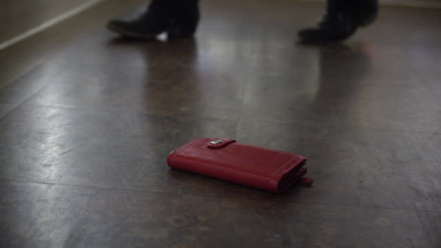 vidéos et rushes de tight shot of wallet, on the ground in a grocery store, is picked up by man. - homme soumis