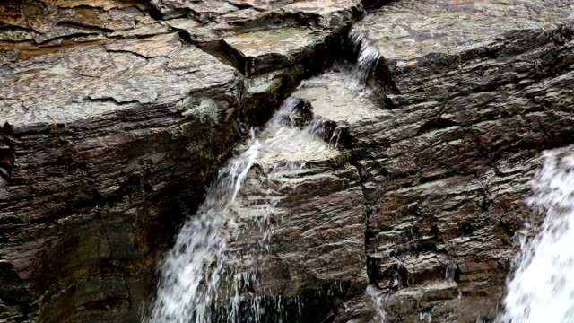 tight shot of water rapids cascading over lichen covered rocks. - mcdonald creek stock-videos und b-roll-filmmaterial