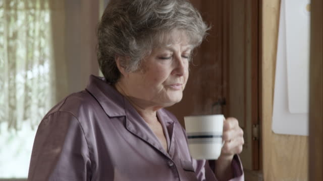 Tight shot of woman drinking hot beverage in pajamas.