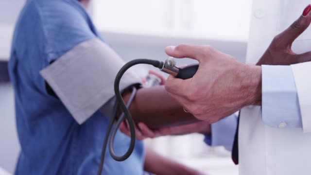 tight shot of young md checking senior womans blood pressure with stethoscope - blood pressure gauge stock videos & royalty-free footage
