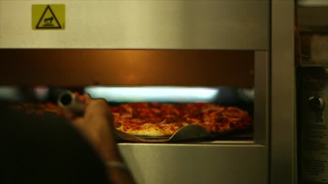 vidéos et rushes de a tight slow motion shot of a dominos employee taking a pizza out of the oven in ann arbor michigan on october 9 a slow motion tight shot of a... - positionner