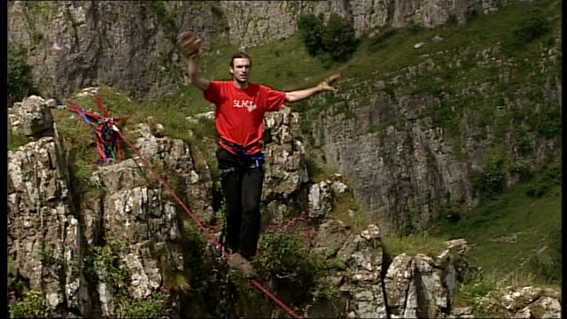 tightrope walk across cheddar gorge; england: somerset: cheddar gorge: ext shot looking at tightrope ribbon stretched 95ft across cheddar gorge nylon... - tightrope walking stock videos & royalty-free footage