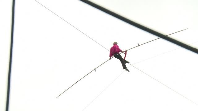 vídeos y material grabado en eventos de stock de tightrope walker denis josselin attempts to cross the seine on a wire thats 175 metres long - alambre
