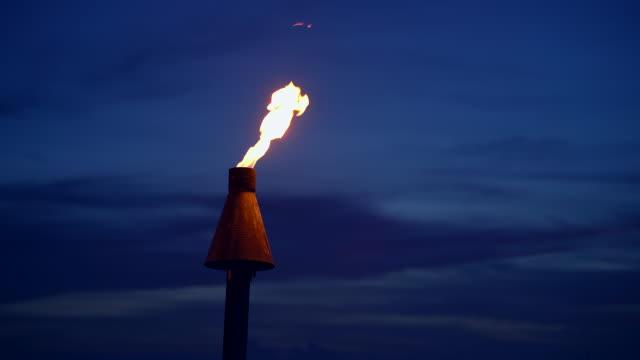 stockvideo's en b-roll-footage met tiki torch flame in de schemering - tiki torch