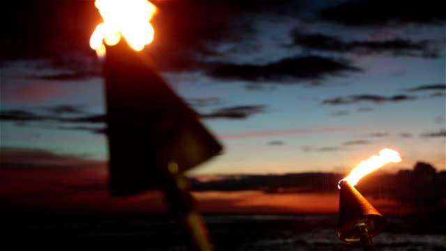 stockvideo's en b-roll-footage met tiki torch flames on tropical beach at sunset, kauai, hawaii - tiki torch