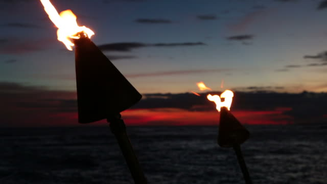 stockvideo's en b-roll-footage met tiki fakkel vlammen op tropisch strand bij zonsondergang, kauai, hawaï - tiki torch