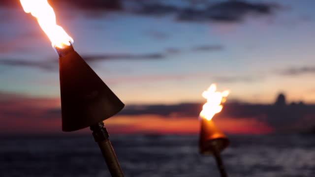 tiki torch flames on tropical beach at sunset, kauai, hawaii - hawaiian culture stock videos & royalty-free footage