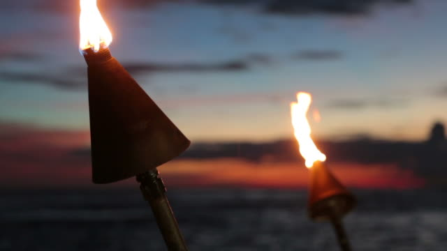 tiki torch flames on tropical beach at sunset, kauai, hawaii - tourist resort stock videos & royalty-free footage