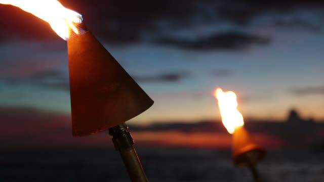 vídeos de stock, filmes e b-roll de tocha tiki chamas na praia tropical ao pôr do sol, kauai, havaí - tocha tiki