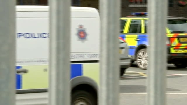man arrested lib england tilbury docks ext police vans along group of police gathered - 犯罪点の映像素材/bロール