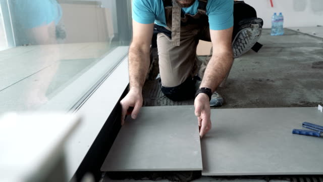tile mason laying floor tiles in new apartment - tile stock videos & royalty-free footage