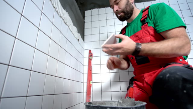 tile mason laying tiles in the bathroom - tile stock videos & royalty-free footage