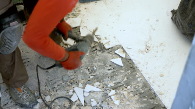 tile mason removing old tiles from the bathroom floor - drill stock videos & royalty-free footage