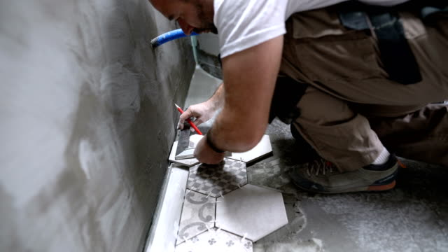 tile professional measuring and preparing tile for installation - tile stock videos & royalty-free footage