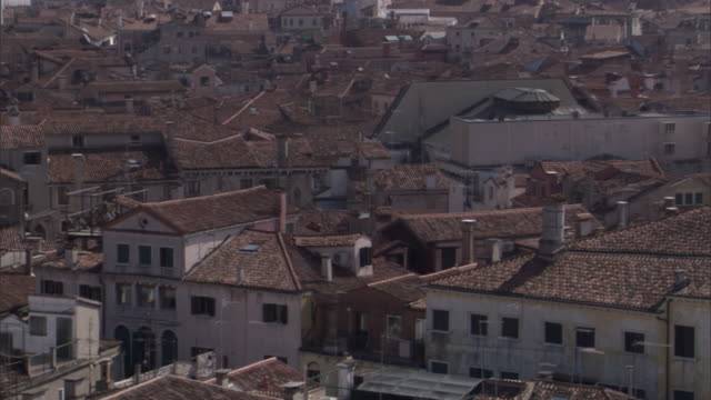tile rooftops stretch to the distant st. mark's basilica in venice. - basilica video stock e b–roll