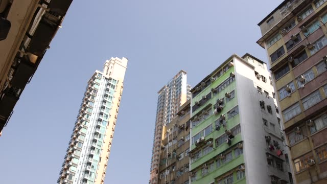vídeos y material grabado en eventos de stock de tile up from traffic driving past old residential buildings to new high rise residential buildings in the sham shui po district of hong kong china on... - kowloon