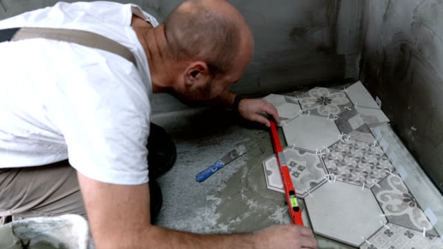 tile worker leveling the floor while installing tiles - bathroom stock videos & royalty-free footage