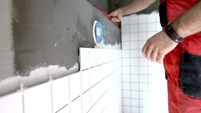 stockvideo's en b-roll-footage met tegel werknemer herverdeling van de muur na het installeren van tegels - installeren