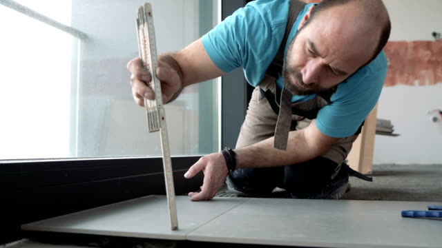 tile worker measuring and leveling the floor tiles - tile stock videos & royalty-free footage