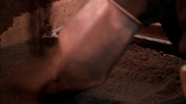 A tile worker smooths clay as it pours into molds.