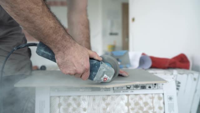 tiler cutting ceramic tile with circular grinder - tile stock videos & royalty-free footage