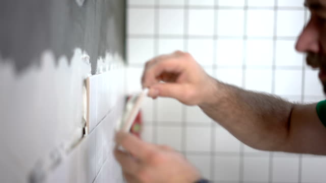 tiler placing ceramic tile on the wall - tile stock videos & royalty-free footage