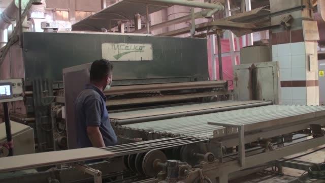 Tiles exit from a kiln onto a conveyor at the Shabbir Tiles Ceramics Ltd production facility in Karachi Pakistan on Wednesday Dec 6 Tiles exit a kiln...