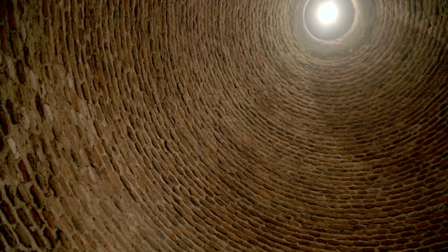 Tilt and pan shot of a huge round brick wall