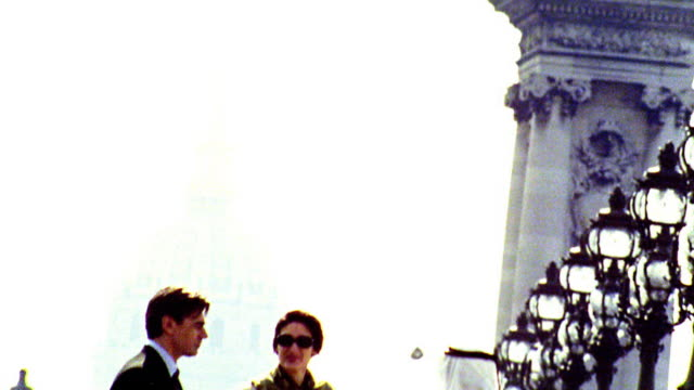 OVEREXPOSED CANTED tilt down 3 businesspeople (1 Arab) talking on Pont Alexandre III / Les Invalides in background