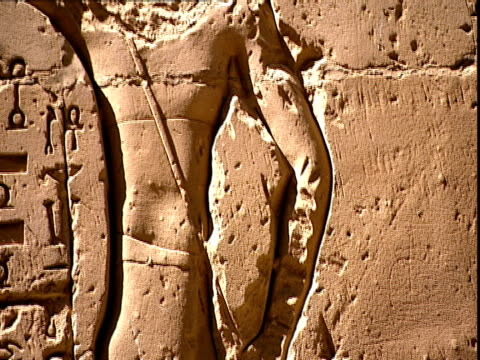 tilt down across a carved relief of a pharaoh to an animal figure hieroglyphs are carved to the left of pharaoh the carving is on the back wall of... - cleopatra stock videos & royalty-free footage