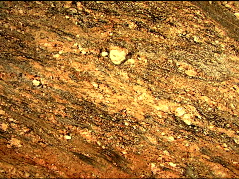 tilt down across warm toned granite stone. - igneous stock videos & royalty-free footage