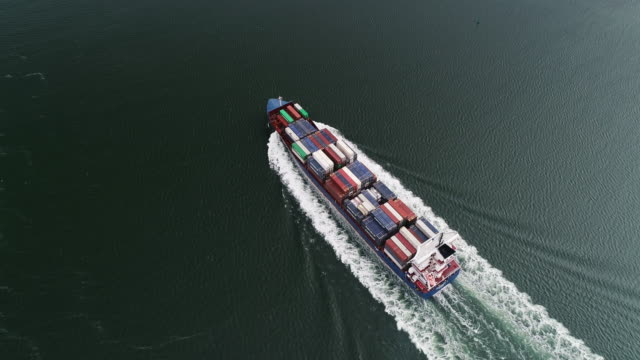vídeos de stock e filmes b-roll de tilt down aerial shot following a container ship, rotterdam, netherlands - navio cargueiro
