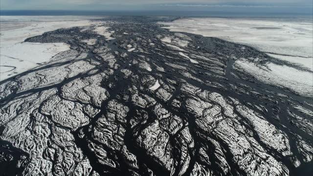 tilt down aerial shot showing a frozen braided river, iceland - woven stock videos & royalty-free footage
