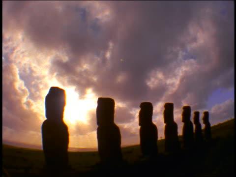 fisheye silhouette tilt down ahu akivi stone statues in front of sun + clouds / easter island - einige gegenstände mittelgroße ansammlung stock-videos und b-roll-filmmaterial