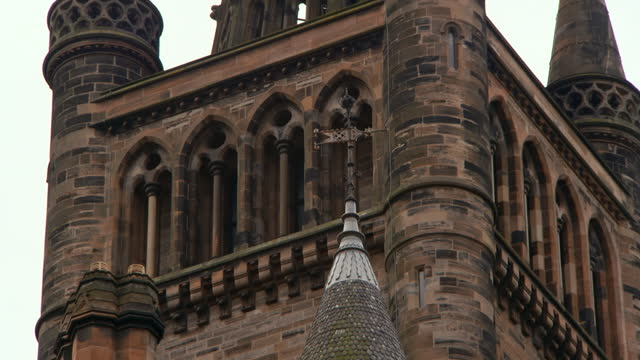 tilt down along the spires and tower of historic glasgow university - stone object stock videos & royalty-free footage