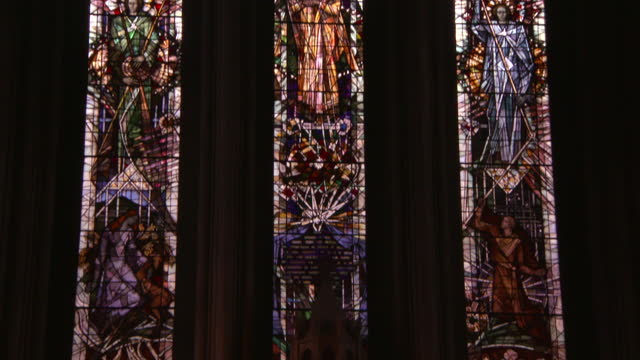 tilt down along three beautiful stained glass windows from inside glasgow cathedral - cathedral stock videos & royalty-free footage