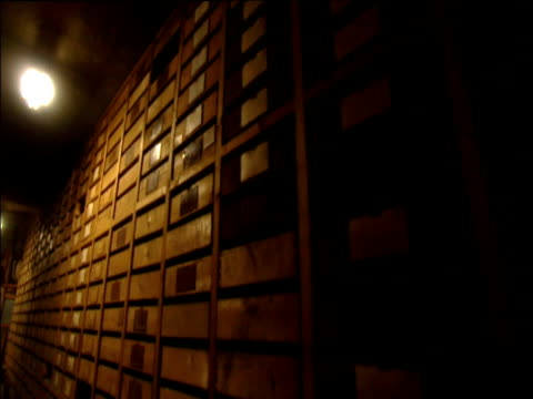 Tilt down and pan left along rows of wooden drawers in basement of dimly lit storeroom