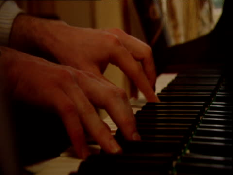 tilt down and pan right to hands playing piano reflected in highly polished wood - pianist stock videos & royalty-free footage