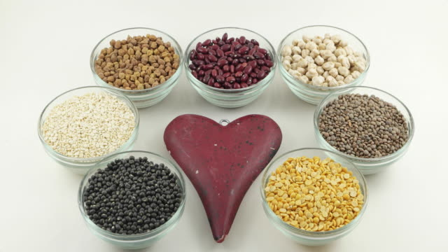 Tilt down and up close up of a red health heart surrounded by various legumes in glass bowls on an isolated white background