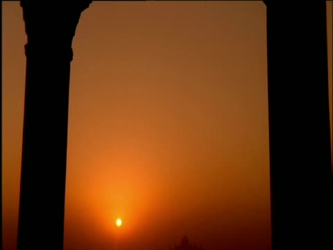 Tilt down arch revealing hazy orange sunset with Taj Mahal in distance Agra