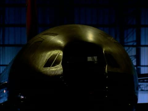 tilt down as aeroplane is reversed in hangar by tow truck - hangar stock-videos und b-roll-filmmaterial