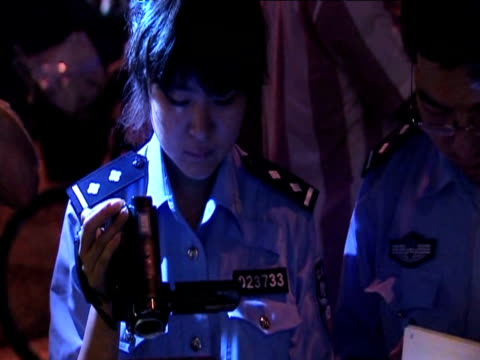 Tilt down as Chinese police officer checks British passport as part of security measures on 20th anniversary of Tiananmen Square massacre China 4...