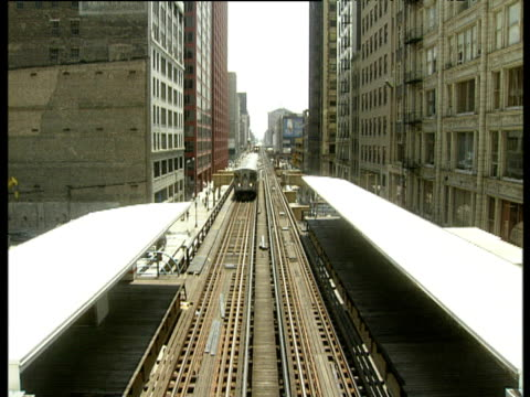 tilt down as elevated train approaches and travels trough station set between skyscrapers chicago. - chicago 'l' stock videos & royalty-free footage