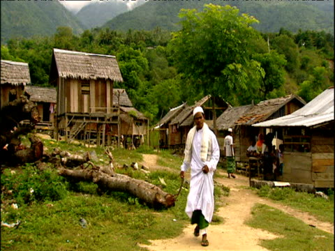 tilt down as muslim man walks along path sulawesi indonesia - strohdach stock-videos und b-roll-filmmaterial