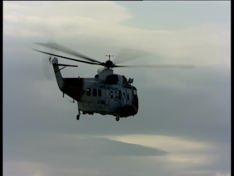 Tilt down as Sea King coastguard rescue helicopter hovers and descends