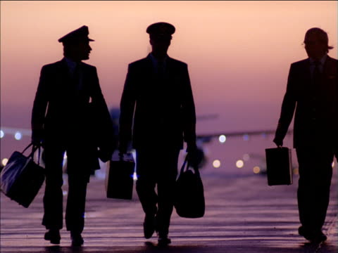 tilt down as silhouetted pilots walk along runway with aircraft in background - pilot stock videos and b-roll footage