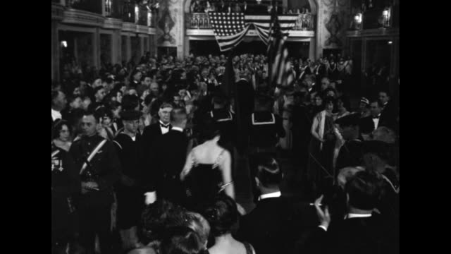 ballroom packed with people in formal wear / MS two men walk down center aisle toward flag draped balcony followed by color guard followed by two...