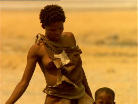 Tilt down Basarwa tribeswoman standing with children, Botswana