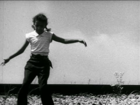 b/w 1951 tilt down black girl running down hill + picking up toy boat in water in reeds / documentary - girls stock videos & royalty-free footage